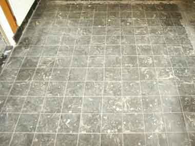 de tegelvloer gelijmd tapijt gezeten dit tapijt is al verwijderd