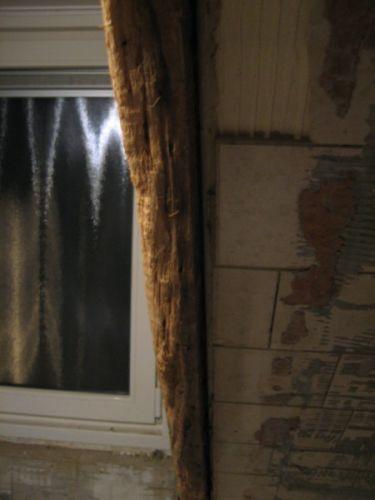 Houten steunbalk achter gipsplaten met tegels in badkamer
